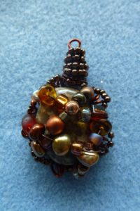 Wrap more beaded wire around to enclose a larger bead in the centre