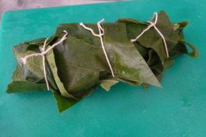 Wrap salmon fillet in leaves and tie parcel with string