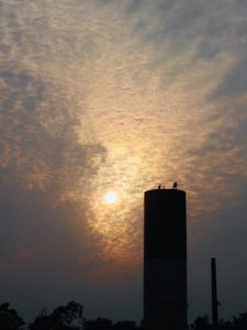Water tower cleaners with amazing sky