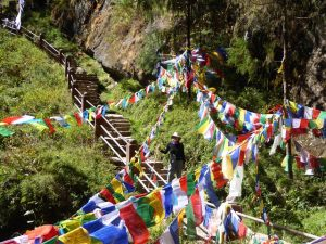 Doreen amongst the prayer flags at the waterfall